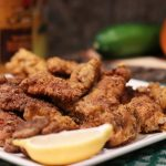Creole fried catfish nuggets on a plate with lemon wedges